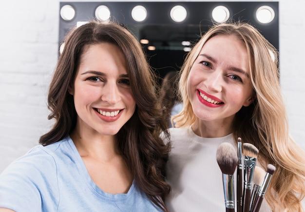 Twee glimlachende vrouwen met borstels die selfie bij make-upspiegel nemen Gratis Foto