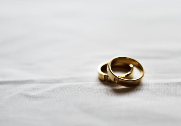 Twee gouden trouwring op witte achtergrond Gratis Foto