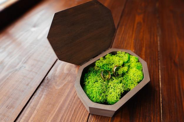 Twee gouden trouwringen in een mooie geschenkdoos op hout Premium Foto