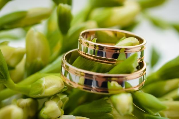 Twee gouden trouwringen liggen aan de bloemen van een mooi boeket Premium Foto