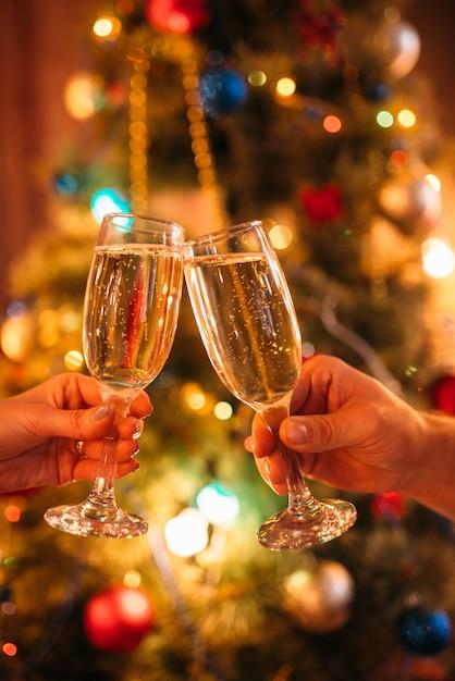 Twee handen gerinkelglazen met champagne, kerstmis Premium Foto