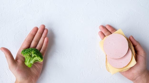 Twee handen met broccoli en een sandwich. idee voor gezond eten. lichte achtergrond Gratis Foto