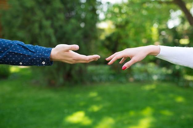 Twee handen raken de verbinding van romantische minnaars Premium Foto