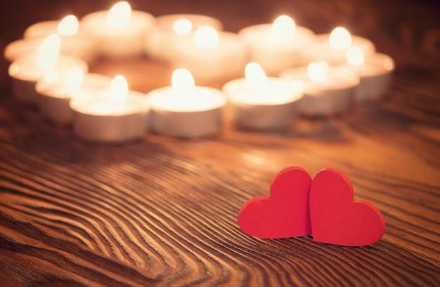 Twee harten, brandende kaarsen op houten. valentijnsdag Premium Foto