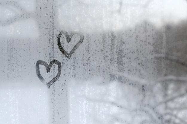 Twee harten die op misted glas in de winter worden geschilderd Premium Foto