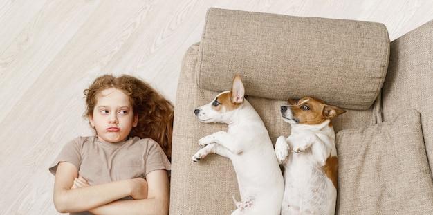 Twee honden slapen op beige bank en ongelukkig meisje liggend op de houten vloer. Premium Foto