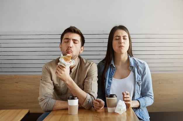 Twee hongerige studenten na een lange dag hard studeren met een maaltijd in de cafetaria. jong paar dat met grote tevredenheid sandwiches eet. Gratis Foto