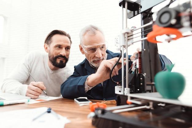 Twee ingenieurs drukken de details af op de 3d-printer. Premium Foto