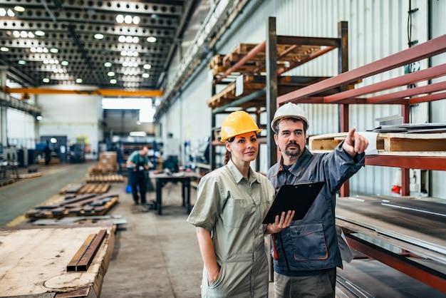 Twee ingenieurs, een man en een vrouw, in de fabriek bespreken. Premium Foto