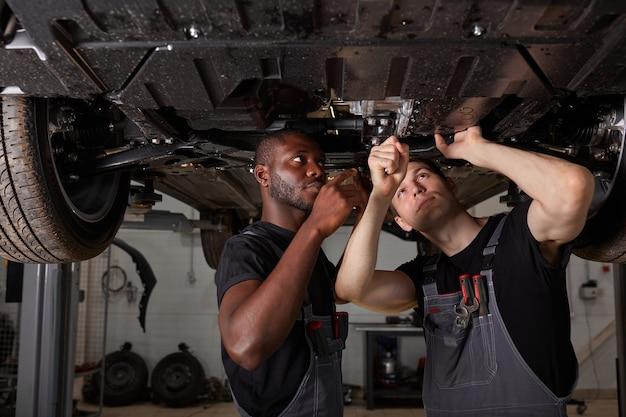 Twee interraciale diverse monteurs die autobodem in autodienst controleren Premium Foto