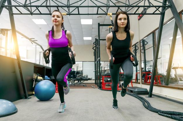 Twee jonge aantrekkelijke fitness vrouwen doen cross fit met riemen systeem Premium Foto