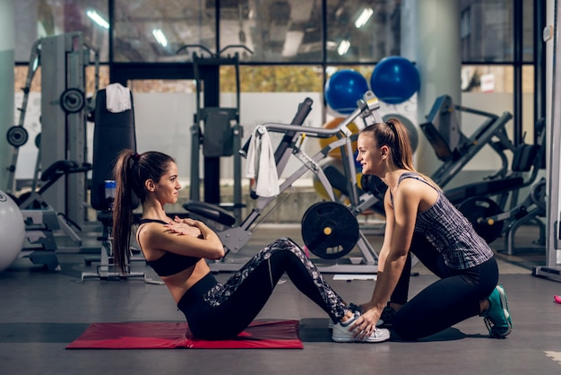 Twee jonge aantrekkelijke vrolijke sportieve actieve meisjes doen push-ups in een team in de moderne sportschool. Premium Foto