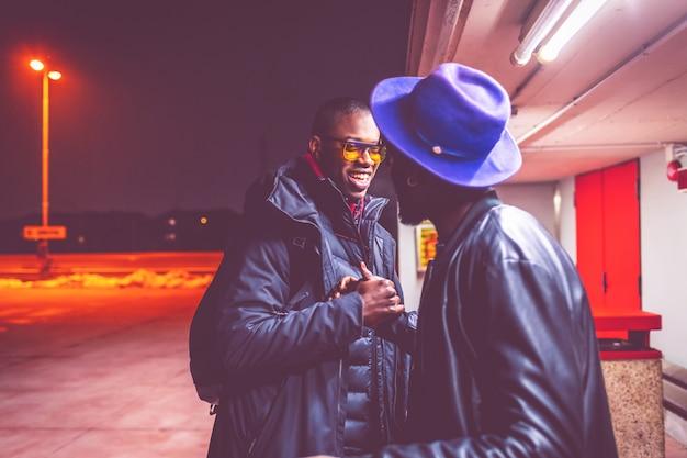 Twee jonge afrikaanse mannen buiten groeten Premium Foto