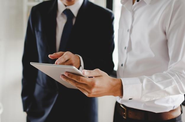 Twee jonge bedrijfsmenseninvesteerder in kostuum die en informatie over financieel nieuws spreken lezen Premium Foto