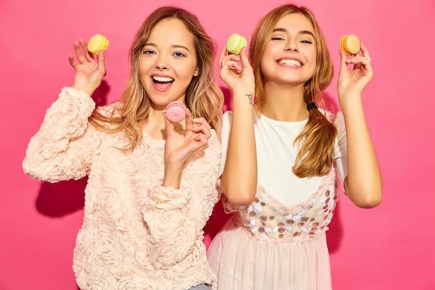 Twee jonge charmante mooie glimlachende hipster vrouwen in trendy zomerkleren. vrouwen met kleurrijke makarons, die macarons houden dichtbij gezicht. poseren op roze muur Gratis Foto
