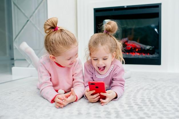 Twee jonge gefocuste kinderen spelen een smartphone zonder naam op de vloer van de woonkamer. jonge kinderen en techniek, zussen spelen met een mobiele telefoon, bekijken video's of spelen spelletjes Premium Foto