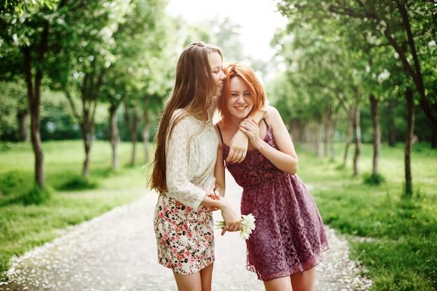 Twee jonge gelukkige meisjes plezier in het park Premium Foto