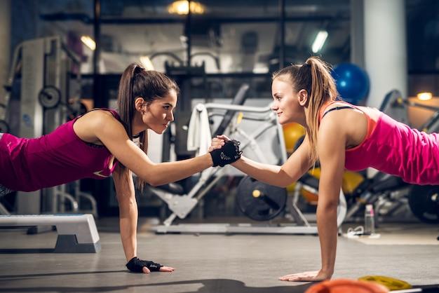 Twee jonge gemotiveerde agressieve aantrekkelijke gerichte sportieve actieve vrouw doen push-ups en houden handen bij elkaar terwijl ze elkaar in de moderne sportschool kijken. Premium Foto