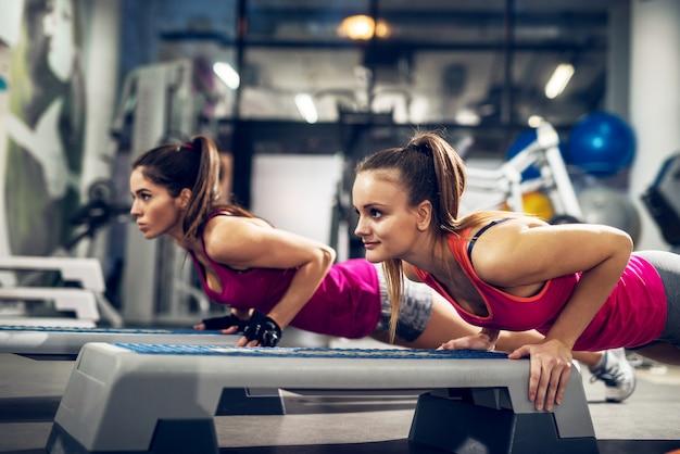 Twee jonge gemotiveerde atletische aantrekkelijke gerichte sportieve actieve vrouw doen push-ups op steppers in de moderne sportschool. Premium Foto