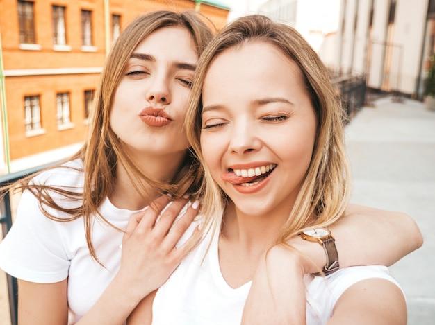 Twee jonge glimlachende hipster blonde vrouwen in de zomerkleren. meisjes nemen selfie zelfportretfoto's op smartphone. . Gratis Foto