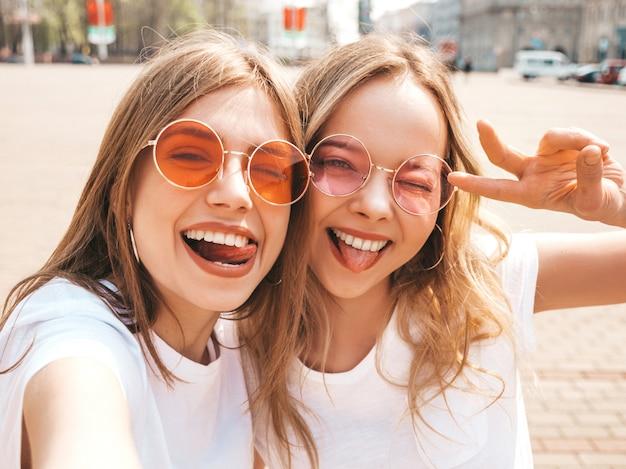 Twee jonge glimlachende hipster blonde vrouwen in kleren van de de zomer de witte t-shirt. meisjes die selfie zelfportretfoto's op smartphone nemen modellen die op straat stellen positief wijfje die hun tong tonen Gratis Foto