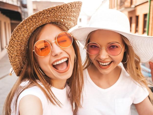Twee jonge glimlachende hipster blonde vrouwen in kleren van de de zomer de witte t-shirt. meisjes nemen selfie zelfportretfoto's op smartphone. Gratis Foto