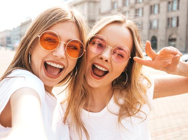 Twee jonge glimlachende hipster blonde vrouwen in kleren van de de zomer de witte t-shirt. Gratis Foto