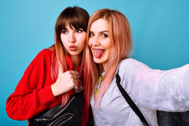 Twee jonge grappige mooie hipster-vrouwen die sportieve, lichte casual outfits dragen, lachend gillend en gedag zeggen, blauwe muur Gratis Foto