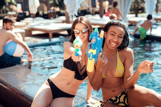 Twee jonge lachende vrouwen in bikini bij zwembad Premium Foto