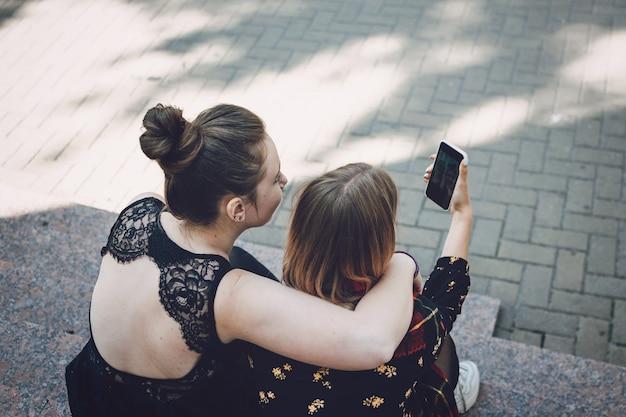Twee jonge lesbiennes meisjes knuffelen en nemen selfie op smartphone buitenshuis. Premium Foto