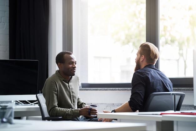 Twee jonge mannelijke collega's met elkaar praten Gratis Foto