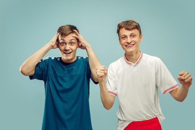 Twee jonge mannen die zich in sportkleding bevinden die op blauw worden geïsoleerd Gratis Foto