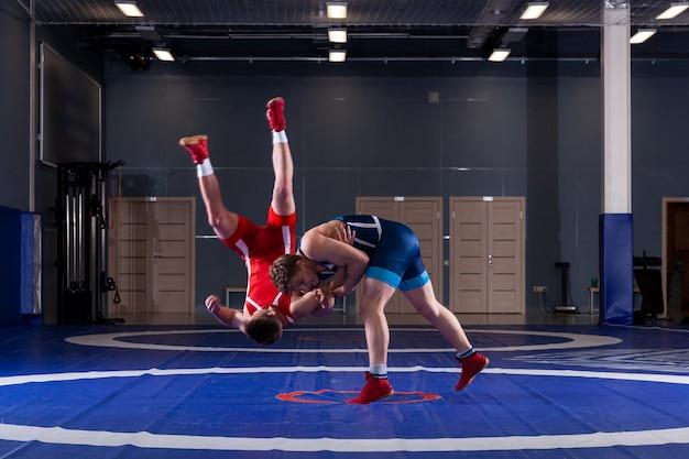 Twee jonge mannen in blauwe en rode worstellegging worstelen en maken een suplex worstelen Premium Foto