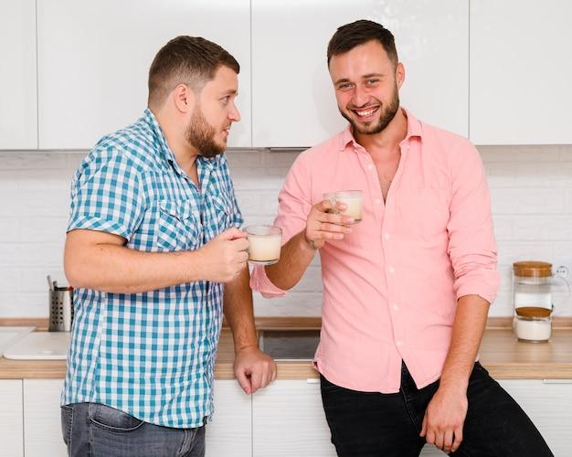 Twee jonge mannen met koffie in de keuken Gratis Foto