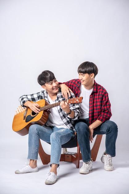 Twee jonge mannen zaten op een stoel en speelden gitaar. Gratis Foto