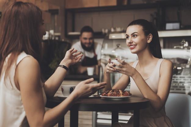 Twee jonge meisjes communiceren in een café aan de tafel Premium Foto