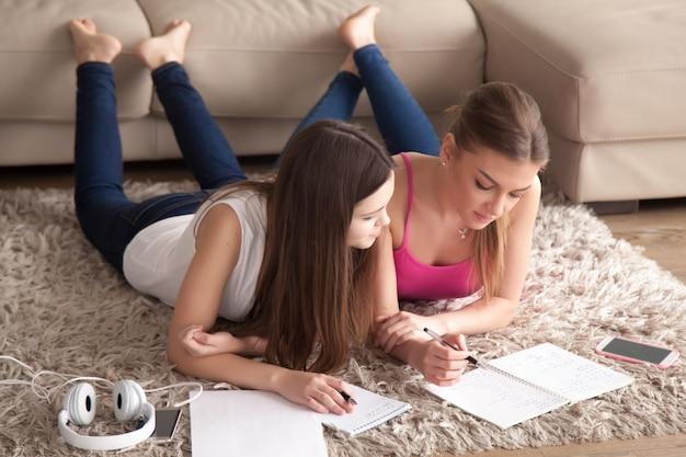Twee jonge meisjes die op tapijt liggen, die nota's in blocnotes nemen. Gratis Foto
