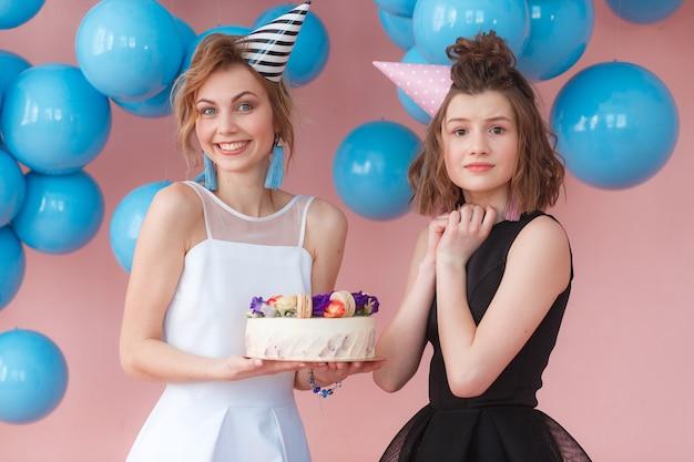 Twee jonge meisjes die verjaardagstaart houden en tonen zeer opgewekte emotie Gratis Foto