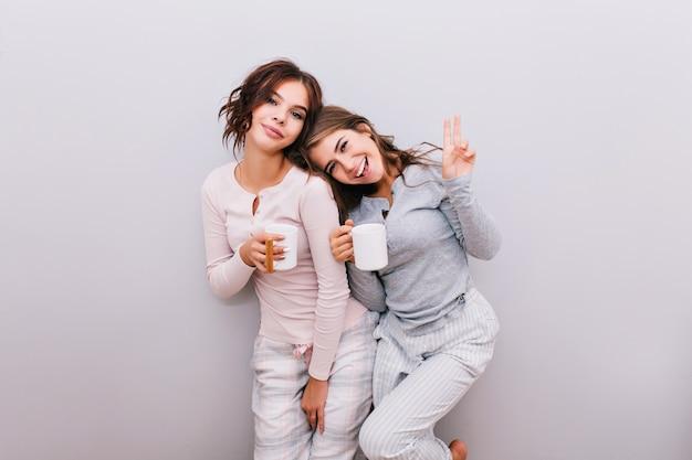 Twee jonge meisjes in pyjama's met kopjes op grijze muur. meisje met lang haar mager hoofd op schouder van meisje met krullend haar. ze glimlachen. Gratis Foto
