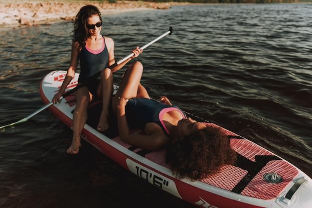 Twee jonge meisjes leggen samen op surf. Premium Foto
