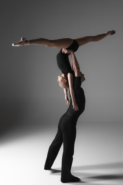Twee jonge moderne balletdansers op grijze studioachtergrond Gratis Foto