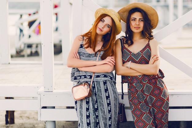 Twee jonge modieuze vrouwen in strohoed en stijlvolle zomer outfit poseren in de buurt van tropische strandbar Gratis Foto