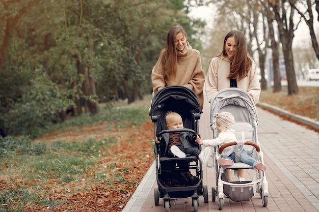 Twee jonge moeders lopen in een herfst park met rijtuigen Gratis Foto