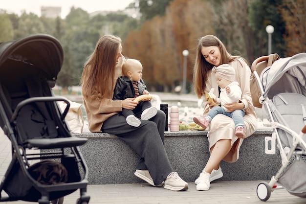 Twee jonge moeders zitten in een herfst park met rijtuigen Gratis Foto