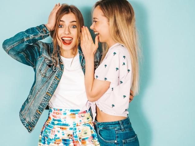 Twee jonge mooie blonde glimlachende hipster meisjes in trendy zomer casual kleding. Gratis Foto