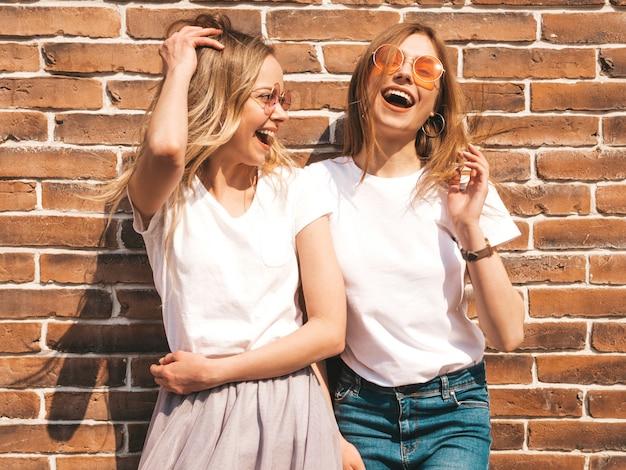Twee jonge mooie blonde glimlachende hipster meisjes in trendy zomer wit t-shirt kleding. . positieve modellen die pret in zonnebril hebben Gratis Foto