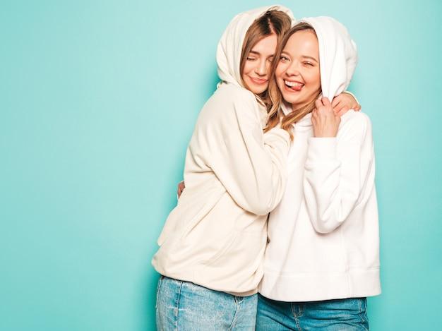 Twee jonge mooie blonde lachende hipster meisjes in trendy zomer hoodie kleding. sexy onbezorgde vrouwen die dichtbij blauwe muur stellen. trendy en positieve modellen hebben een tongteken in een zonnebril Gratis Foto