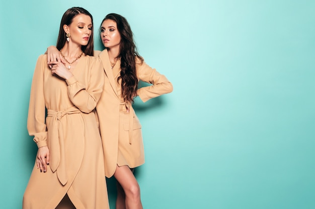 Twee jonge mooie brunette meisjes in mooie trendy zomer kleding. sexy zorgeloze vrouwen poseren in de buurt van blauwe muur in studio Gratis Foto