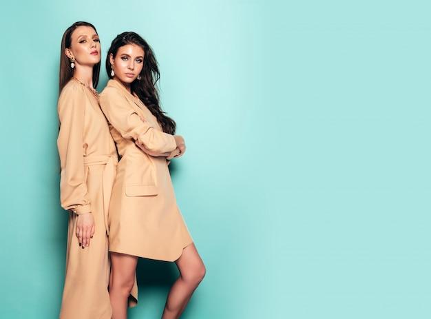 Twee jonge mooie brunette meisjes in mooie trendy zomerkleding. sexy zorgeloze vrouwen poseren in de buurt van blauwe muur in studio. vrouwelijke knuffel elkaar Gratis Foto