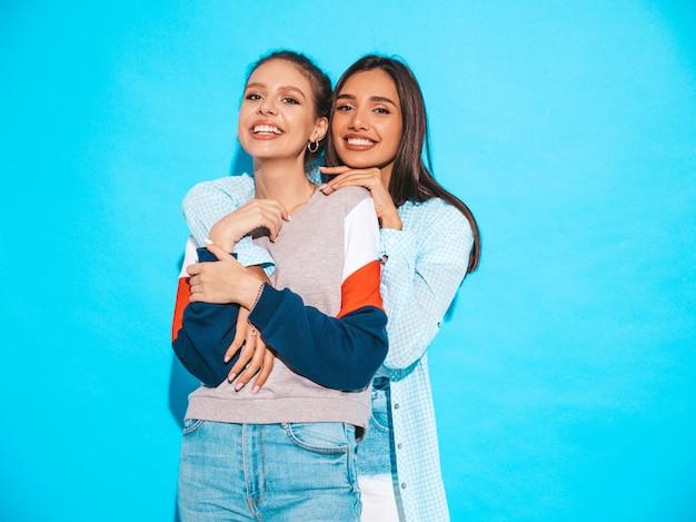 Twee jonge mooie glimlachende blonde hipstermeisjes in kleren van de trendy de zomer kleurrijke t-shirt. sexy onbezorgde vrouwen die dichtbij blauwe muur stellen. positieve modellen hebben plezier Gratis Foto